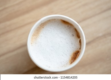 Top view of takeaway  paper cup of hot coffee latte on wooden table..