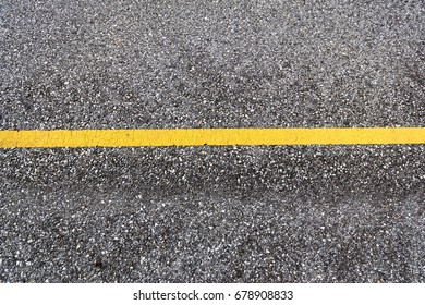 Top view of a tarmac road surface with horizontal yellow line as background