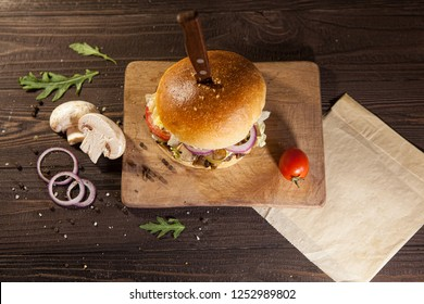 Top view of tasty beaf and mushroom hamburger on dark wooden board pierced with knife, surrounded by cherry tomato. Free space for text