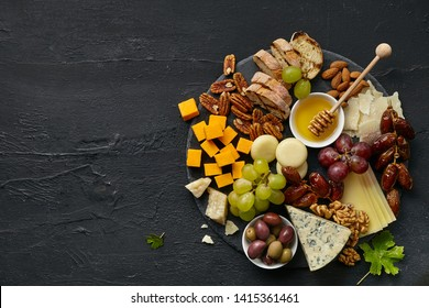 Top view of tasty cheese plate with fruit, grape, nuts and honey on a circle kitchen plate on the black stone background, top view, copy space. Gourmet food and drink.
