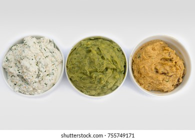 Top view of tasty dip bowls, white cottage cheese with sesame and chive seasoning, green guacamole bowl and homemade hummus