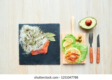 Top view of a tasty fresh salted salmon fillet with crispbread and avocado on wooden board. Aromatic herbs, spices and vegetables - healthy food, diet and cooking concept. Perfectionism.