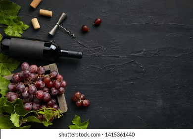 Top view of tasty fruit plate with the wine bottle on the black stone on a kitchen plate on the black stone background, top view, copy space. Gourmet food and drink.