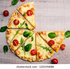 top view of tasty sliced pizza with tomatoes and herbs without two slices over wooden table background