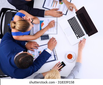 Top view of a team of office workers pointing at a laptop