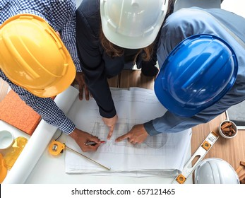 Top view teamwork concept, Engineer and workers discussing project of new building. ,Team of architects Asian people in group on construction site check documents and business workflow.