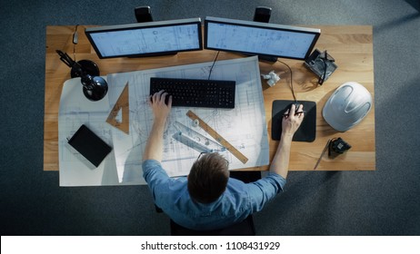 Top View of a Technical Engineer Working on His Blueprints, Drawing Plans, Using Desktop Computer. Various Useful Items Lying on his Table.