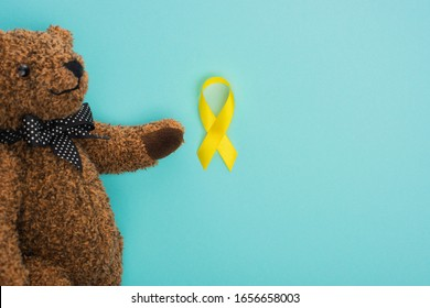 Top view of teddy bear with bow and yellow ribbon on blue background, international childhood cancer day concept