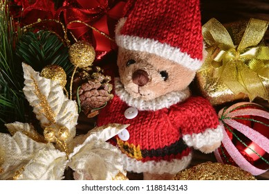 Top view of Teddy Bear wearing Santa Claus knitted sweaters with gift boxes on wooden background. Concept about season greetings. Merry Christmas and New Year Celebration with copy space. Rustic Style