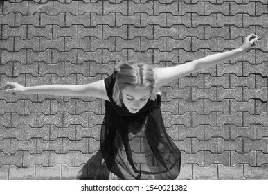 The top view of the teen ballerina on gray cobblestone background. young black bride. raise hands. closed eyes.