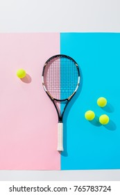 top view of tennis racket and yellow balls on blue and pink papers