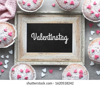 """Top view, text """"Valentinstag"""" on blackboard in German means """"Valentines day"""". Blackboard framed with sugar-sprinkled muffins with pink and white fondant icing hearts. - Shutterstock ID 1620518242"""