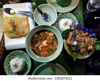 Top view Thai food; Green curry in omelette,Sour soup made of Tamarind Paste,Pomelo salad thai style