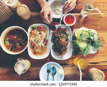 Top view Thai food on table: Eating north eastern foods (SOM TUM - Spicy Papaya Salad, Sticky rice, NUM TOK - Spicy Soup). Local and traditional way. Thai Food Background. enjoy eating concept