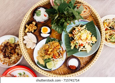 Top view of Thai signature food. Papaya salad with another local food like Pad Thai and fried rice with grill pork, tambourine on the wood table. Traditional Thai popular food vegetable