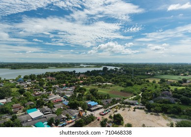 Top view of Thai village with houses, trees and a river run through with blue sky white clouds as background