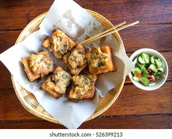 Top view of thailand food fried bread with minced pork spread in basket on wood table.