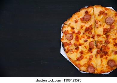 Top view of thin pepperoni pizza on right frame on white paper and dark background