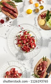Top view - thin slices of deli meats veal venison on transparent flat plate on white rustic isolated copyspace background with ingredients