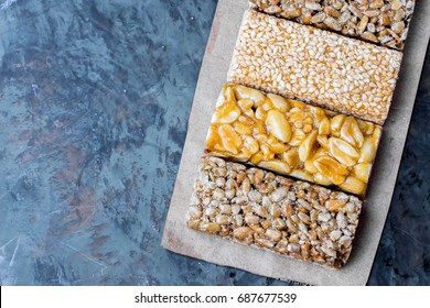 Top view of three bars Nuts in caramel, honey on gray table background. Snack food. Unhealthy eating. Copy space