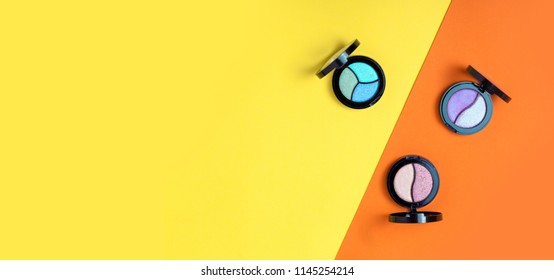 Top view of Three Eye shadows pallets and applicators on yellow and orange background. Fashion cosmetic set. Top view. Copy psace for text.