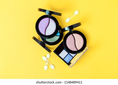 Top view of Three Eye shadows pallets and applicators on yellow background. Fashion cosmetic set. Top view.