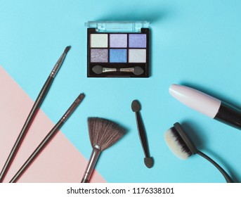 Top view of Three Eye shadows pallets and various make up brushes on yellow background. Fashion cosmetic set. Flat lay. Trendy make up picture