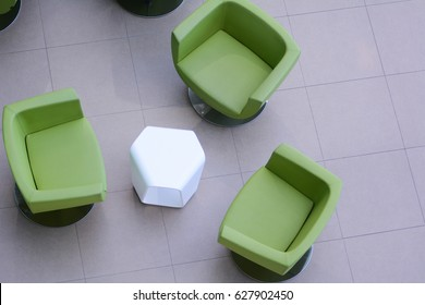 Top view of three green armchairs with a white table. Place for waiting or business