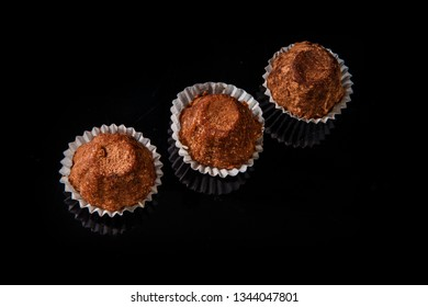 top view of three healthy useful organic handmade chocolate candies decorated with brown cocao powder on black mirror background
