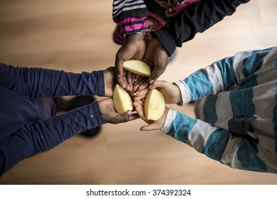 Top view of three kids of mixed races each holding a piece of apple in the palms of their hands.