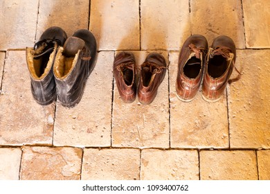 Top view of three pairs of old worn leather shoes in a line on beige stone floor.