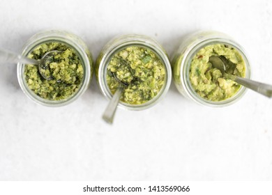 Top view of three pestos in glass jars: avocado, hemp seeds and pumpkin seeds pesto; almond, mint and basil pesto: walnut, kale and parsley pesto served with a spoon on light background. Flat lay.