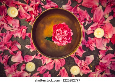 Top view tibetan singing bowl with floating inside in water pink peony flower. Burning candles and petals on the black stone background. Meditation and Relax. Exotic massage. Flatlay. Selective focus