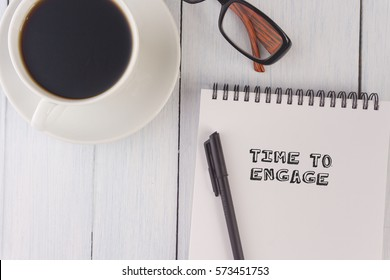 top view of time to engage written on notebook,pen,coffee,glasses on the white desk