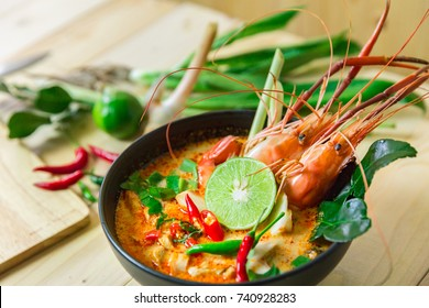 "Top view ""Tom Yum Kung"" on wooden background, It's local in Thai food, Prawn soup is popular and famous food, I'ts delicious amazing taste hot and spicy."