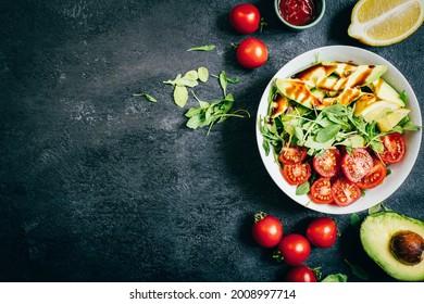 top view of tomato salad arugula avocado lemon in white plate on black background