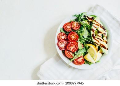 top view of tomato salad arugula avocado lemon in white plate on light background