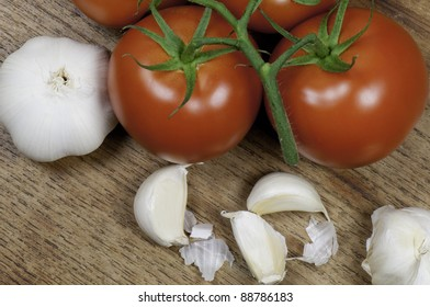 Top view of tomatoes and garlic on a wooden table top.