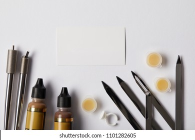 top view of tools for permanent makeup and white paper isolated on white