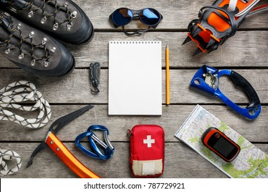 Top view of tourist equipment for a mountain trip on a rustic light wooden floor with a notebook and an empty space in the middle.