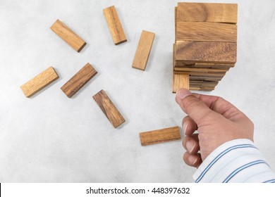 Top view of the tower stack from wooden blocks toy and man's hand take one block