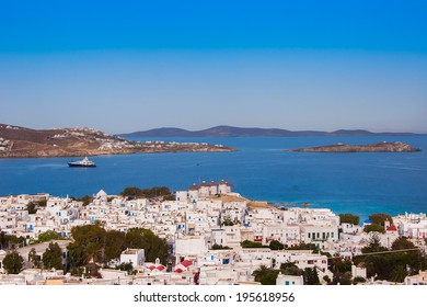 Top view of the town and port of Mykonos Island and a sailing boat in the blue sea ...