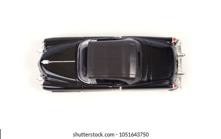Top view of toy model classic car on white background.