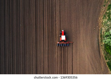 Top view of tractor planting corn seed in field, high angle view drone photography