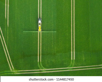 Top view of tractor spraying green field