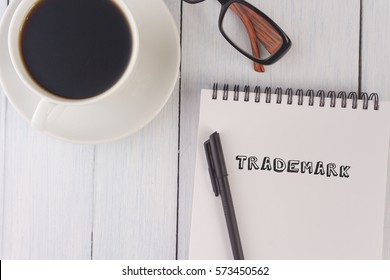 top view of trademark written on notebook,pen,coffee,glasses on the white desk