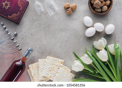 top view of traditional book with text in hebrew and matza on concrete table