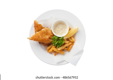 Top view of traditional British style fish and chips including deep fried cod, french fries, lemon, and tartar sauce in ceramic dish isolated on white background