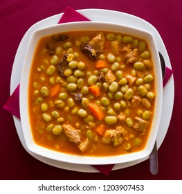 Top view of traditional Catalan stewed beans with pork meat, black sausage and vegetables served in white bowl