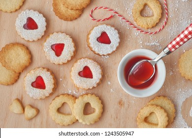 Top view of traditional Christmas Linzer cookies filled with strawberry jam on wooden board. These are traditional Austrian filled bisquits.